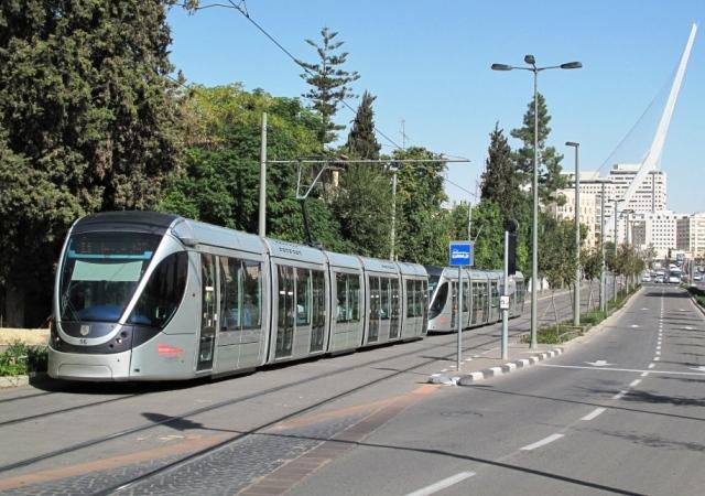 """Un binôme de rames Citadis 302 Alstom, rame numéro 16 en tête, circulant en direction du terminus """"Mount Herzl"""", est photographié sur la ligne rouge de Jérusalem à l'approche de la station """"Kiryat Moshe"""". En arrière plan, le mât incliné de 119 mètres de haut du Pont de Cordes de l'architecte espagnol Santiago Calatrava Valls. Photo prise le lundi 2 novembre 2015. Copyright : Jaco"""