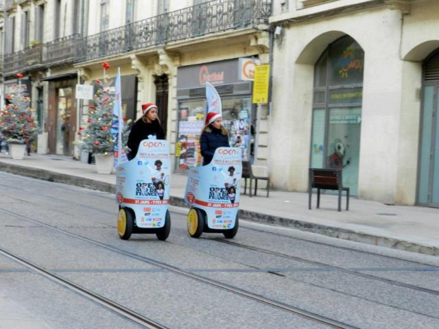 Deux gyropodes, pilotés par deux charmantes jeunes filles, passent à la hauteur du 17 boulevard du Jeu-de-Paume à Montpellier, au grand étonnement d'Adèle, la coccinelle, mascotte du chantier de bouclage de la ligne 4 de tramway, le samedi 12 décembre 2015. Copyright : Anje34