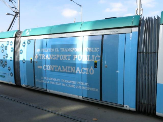 """A l'instar du pelliculage appliqué sur un module de la rame 03 Citadis 302 Alstom du réseau Trambaix de Barcelone, le ColL5ctif ligne 5 de Montpellier devrait faire sien le slogan : """"Plus de transports publics = Moins de pollution :"""". Photo prise le mardi 26 janvier 2016. Copyright : Edgar Chaptal"""